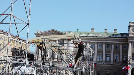 eljárás : Men building stage for event on street. Workers fix iron balks to construction. Sunny evening. Stock mozgókép