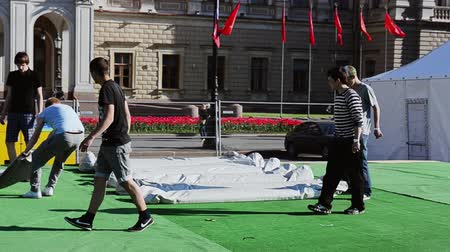 eljárás : Men building stage on street. Workers carry heavy sack , lay on green carpet. Sunny day.