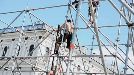 eljárás : Men building stage for event on street. Workers raise ladder. Iron balks. Sunny evening.
