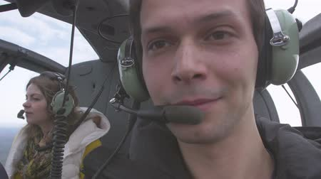 pilot in command : Man in earphones with microphone shoot himself in flying helicopter. Young girl on back seat. Flight. Transportation Stock Footage