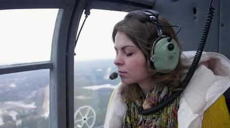 pilot in command : Girl in earphones with microphone seat flying helicopter. Noise. Transportation. Above ground. Daylight