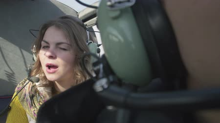 pilot in command : Girl in earphones with microphone smile, blink in camera in flying helicopter. Noise. Transportation. Above ground