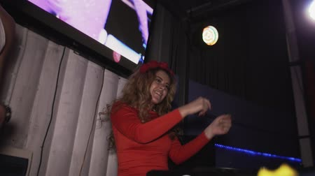 mc : Happy dj girl in red dress dance at turntable in nightclub with mc man. Raise hands. Slow motion Stock Footage