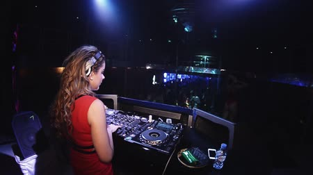 mc : Dj girl in red dress spinning at turntable in nightclub. Headphones. Mixer. Holidays