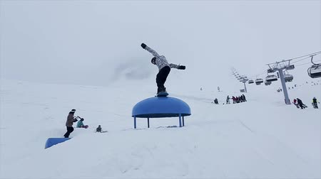 esqui : Snowboarder ride from slope jump over springboard. Ski resort in snowy mountains. Contest. Snow falls. Slow motion