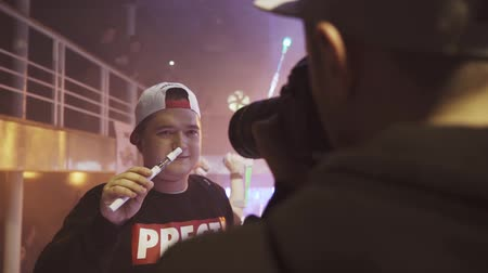 boates : Boy with electronic cigarette posing to photographer in nightclub. Party. Spotlights. Vaper. Slow motion Stock Footage
