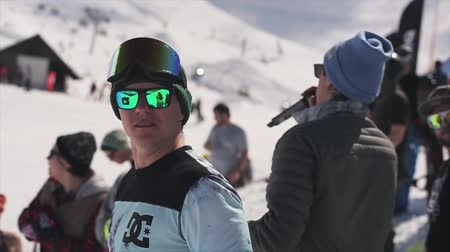 hat : Man speak in microphone at ski resort. Boy in reflected sunglasses look in camera. People. Sunny day. Slow motion
