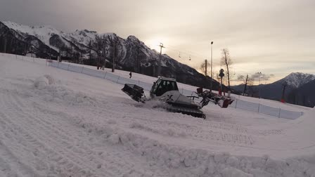 snowcat : Quadrocopter shoot snowcat make snow trail. Ski resort. People. Evening. Mountains