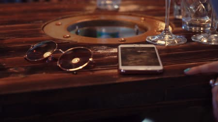 lâmpadas : View of sunglasses, white smartphone, glasses on wooden table in restaurant. Light. Stock Footage