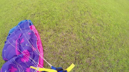 pára quedas : Professional skydiver tie parachute on green field after landing. Extreme sport. Summer