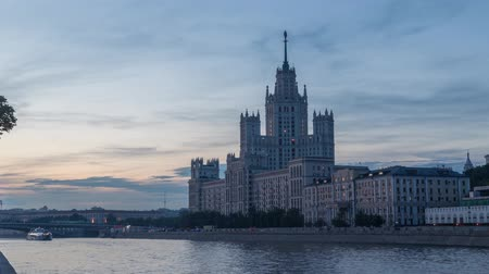 stalinist : Day to night time lapse video of Moskva river with busy ship traffic and stalinist Kotelnicheskaya Embankment Building in Moscow, Russia