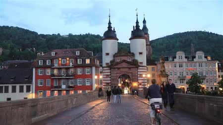 Heidelberg, Germany - May 14 2017: People walk on Old Bridge (Alte Brucke) in front of the Bridge Gate (Bruckentor) at dusk