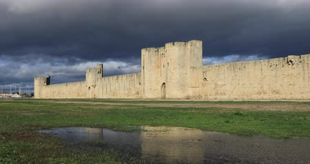 Surrounding wall of Aigues-Mortes medieval fortified city reflecting in water, Occitanie, France Стоковые видеозаписи