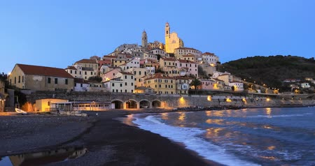 Cervo - medieval hilltop town at dusk, Liguria, Italy (zoom in view from seaside) Стоковые видеозаписи