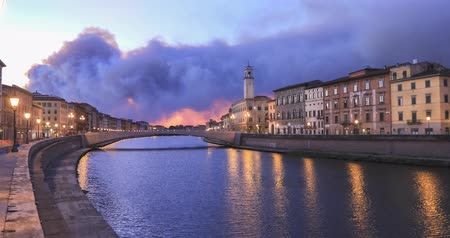 Ponte di Mezzo bridge over Arno river and Clock tower at dusk in Pisa, Italy