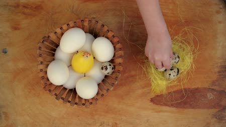 koszyk wielkanocny : Little girl decorating Easter table. Close-up of child hand putting small quail egg into yellow nest. Egg rolling down from wooden desk.