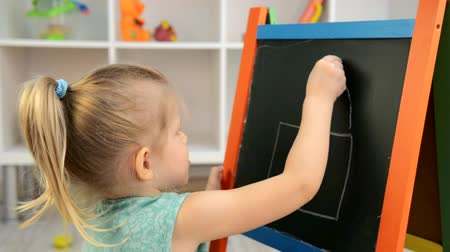 real : Cute little girl drawing house on painting board in the room. Concept of family home and child development. Stock Footage