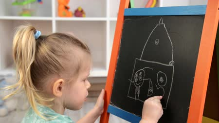 pictured : Pretty small girl drawing heart shape in pictured house. Concept of happy family, relationship and and care.