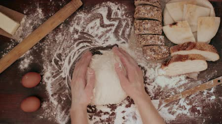 fırınlama : Young woman touching raw bread dough making round shape ready to bake in oven. Wooden table with bread assortment and dough ingredients in rustic kitchen. Stok Video