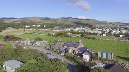 daha fazla : This aerial footage shows a welsh farm house with hills and mountains in the background on a sunny day in Talybont, Wales. It starts stationary and then pulls back to reveal more of the landscape. Stok Video
