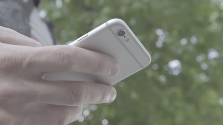 sending : Young man using smartphone outdoor. Close up shot of a mans hands with mobile.