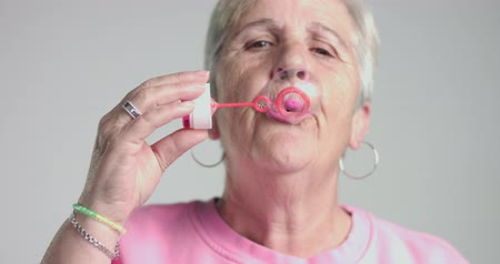 magány : eldery woman blow bubbles to camera