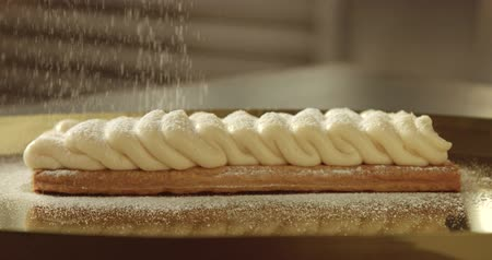 fırınlama : sugar powder falling on a cream on puff pastry base Stok Video