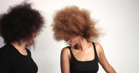 kıvırcık saçlar : couple of black women with huge afro hair dancing and shaking heads Stok Video