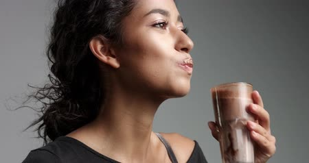 марокканский : Laughing attractive Middle Eastern girl in relaxed black top drinking mocca from a tall glass isolated on gray