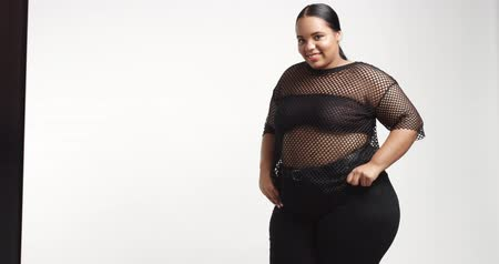 nadváha : Attractive young black plus size model wearing a black fishnet top and black tight pants on white background. beauty plus size curvy model