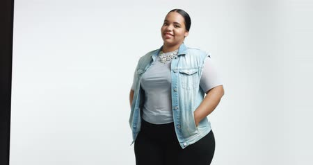 nadváha : Smiling cute big African American girl in blue shirt, black pants and a denim vest isolated on white. casual style plus size model Dostupné videozáznamy