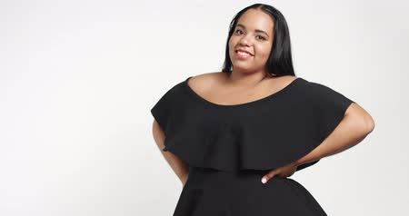 düzgün vücutlu : Confident strong young plus size African American model wearing a black short twirly dress flirting with camera isolated on white Slowmotion from 60fps
