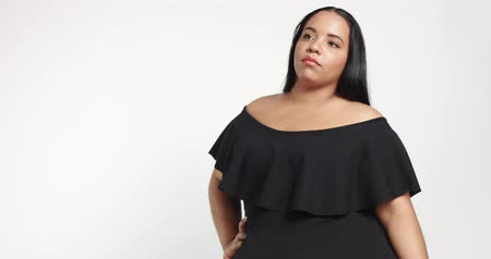 nadváha : Confident strong young plus size African American model wearing a black short twirly dress flirting with camera isolated on white Dostupné videozáznamy
