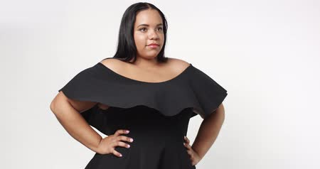 artı : Confident strong young plus size African American model wearing a black short twirly dress flirting with camera isolated on white Stok Video