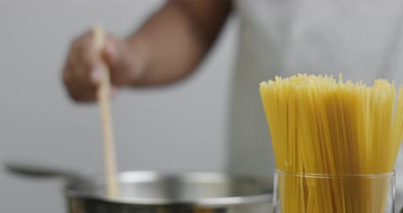 spagetti : Chef mixing something in a large stainless steel pan in the background, bright yellow spaghetti in the foreground