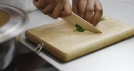spagetti : Dark skinned male chef chopping chives on a rustic wooden cutting board Wideo