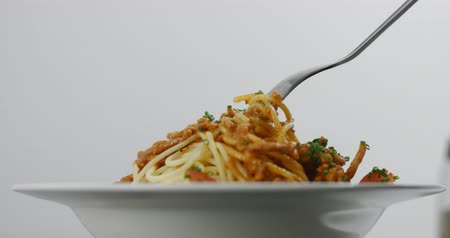spagetti : Fork twisting in succulent hot spaghetti bolognese with chives isolated on white Wideo
