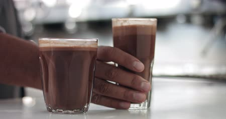 caffe : Close up of a barista in an industrial looking cafe making hot cocoa drinks in glass tumblers