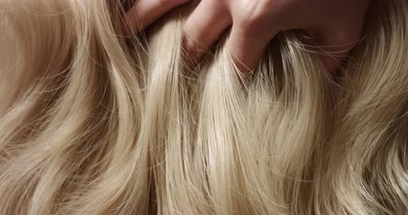 blond vlasy : A womans hand with bright manicure running through long wavy blond hair