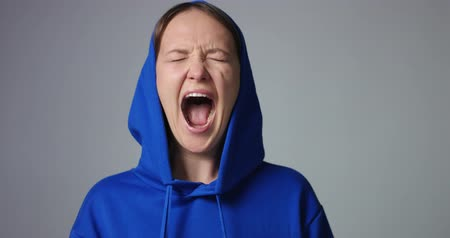 řvát : Young woman in large unlabeled bright blue hoodie screams and acts scared and angry isolated on white