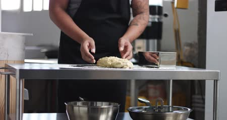 taneli : Dark skinned male chef in a black apron works with bread dough in an industrial looking kitchen