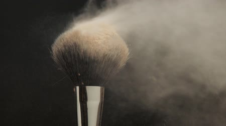 high def : closeup of black brush with a facial powder on it and blowing out by wind