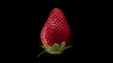 biała czekolada : fresh strawberry on black background and a transparent drop pouring on it. Slowmotion water drop falling on strawberry