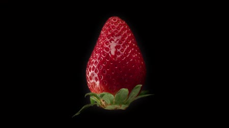 aphrodisiac : fresh strawberry on black background and a transparent drop pouring on it. Slowmotion water drop falling on strawberry