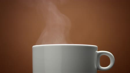 hot beverage : closeup of white cup with hot drink. Steam from cup closeup. Hot coffe. loop