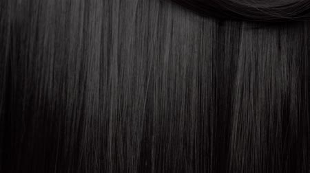 şampuan : Hair texture background, no person. Black shiny hair curl falling down Stok Video