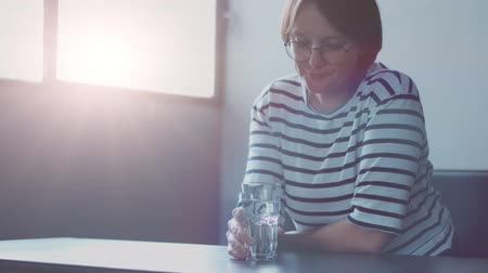 agua : woman in top with stripes drinking water in sunny space with window