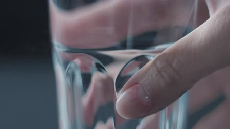 agua : womans hand picking a glass of water closeup with funny nail design Stock Footage