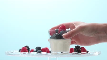 йогурт : woman hand serve putting on a crystal plate glass with greek yogurt with berries