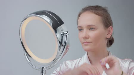 vanity : young woman after facial routin touches her hair an liiking at mirror Stock Footage
